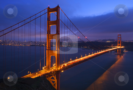 Golden Gate Bridge Sunset Pink Skies Evening with Lights of San  stock photo, Golden Gate Bridge Sunset Pink Skies Evening with Lights of San Francisco California in background by William Perry
