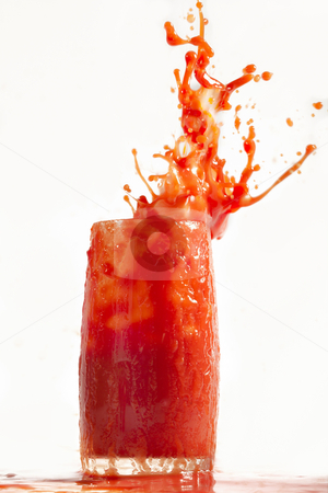Explosion of vitamins stock photo, Sparks of tomato juice from a glass on a white background. by Sergey Goruppa