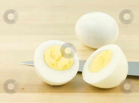 Sliced Egg with Knife stock photo, Sliced egg with knife on a wooden background by John Teeter