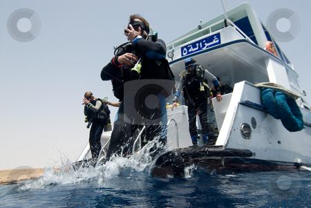Divers entering the water from a dive boat stock photo, Divers entering the water from a dive boat. Red Sea, Egypt. by Mark Doherty