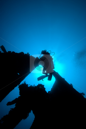 Underneath view of a diver passing through the stern section of  stock photo, Rudder section of the shipwreck Dunraven and diver silhouetted by the sun. Red Sea, Egypt. by Mark Doherty
