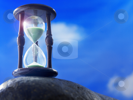 Hourglass stock photo, Hourglass on the rock with blue sky as back ground by eskaylim