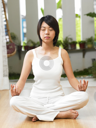 Woman meditating stock photo, Woman practicing yoga at home by eskaylim
