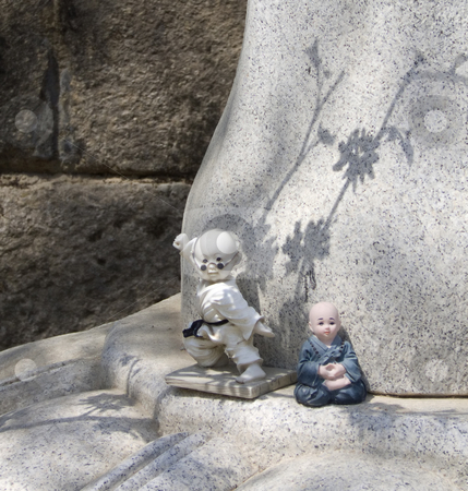 Cartoonish Baby Buddhas stock photo, Two small Buddha figurines left as offerings at a temple in South Korea by Jennifer Vey