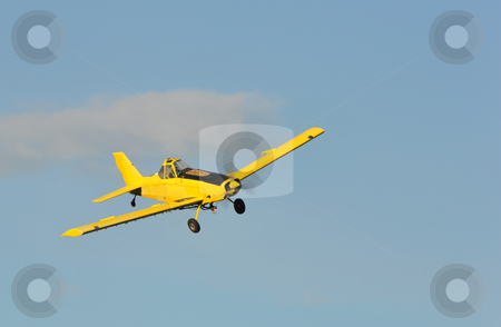 Little plane stock photo, A corp duster or agricultural aircraft flying in a blue sky by Bonzami Emmanuelle