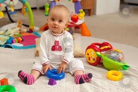 Playmat stock photo, Caucasian baby girl playing on a floor. by Mariusz Jurgielewicz