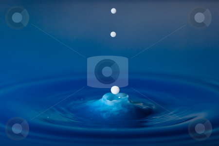 White droplets falling into the blue stock photo, White droplets falling in blue colered water by Dirk Ercken