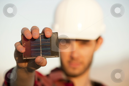 Handsome young man with small solar panel stock photo, Handsome young man wearing hardhat with small solar panel in hand by Scott Griessel