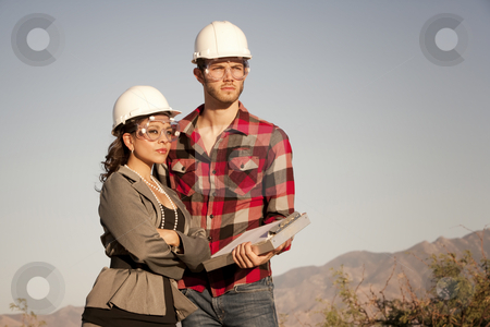 Man and woman in hardhats stock photo, Handsome man and pretty woman outdoors wearing protective hardhats by Scott Griessel