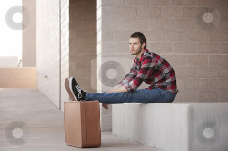 Lanky Young Man stock photo, Lanky Young Man Waiting with Feet Propped on Suitcase by Scott Griessel