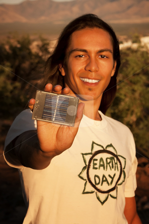 Handsome young man with small solar panel stock photo, Handsome young mixed race man with small solar panel by Scott Griessel