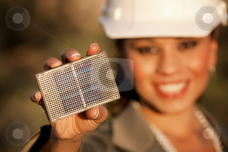 Pretty young woman with small solar panel stock photo, Pretty young woman wearing hardhat with small solar panel in hand by Scott Griessel