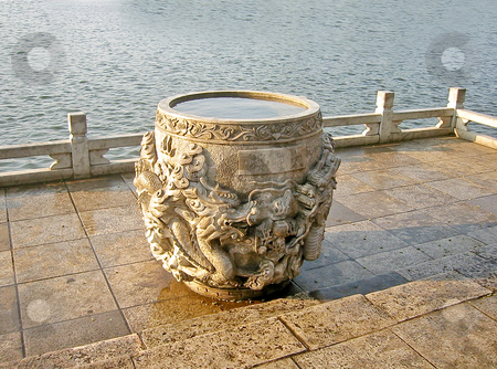 Dragon wishing well stock photo, Stone wishing well filled with rain water by lake by Shi Liu