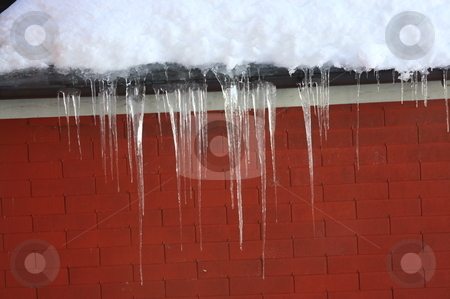 Icicles from the roof stock photo, Icicles dangling from the edge of a roof in front of a red brick wall by Bernard Cruz