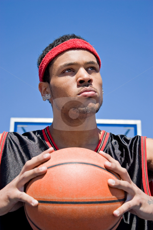 Confident Basketball Player stock photo, A young basketball player gripping the ball tightly. by Todd Arena