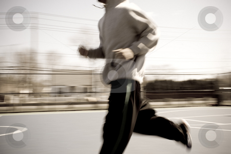 Warm Up Runner stock photo, Abstract blur of a young man warming up by jogging at the basketball court.  Intentional motion blur. by Todd Arena