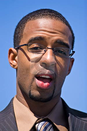 Surprised Business Man stock photo, African American man wearing glasses and a business suit isolated over a blue sky background. by Todd Arena