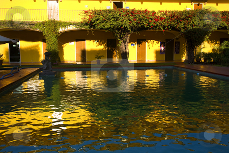 Colors of Mexico Reflections Yellows Blues Reds stock photo, Yellow Adobe Wall Red Bouganvillia, Reflections in Blue Water Guadalajara Mexico