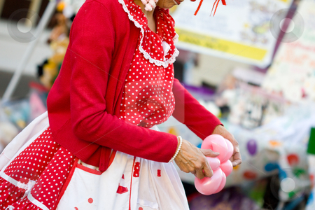 Clown stock photo, Colorful dressed lady clown with a balloon on her hand by Hieng Ling Tie