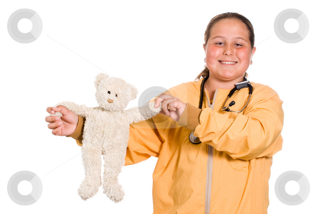 Children's Hospital stock photo, A young girl holding up a stuffed bear while wearing a stethoscope, isolated against a white background by Richard Nelson