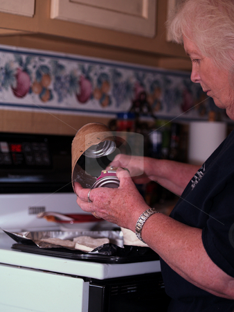 Elderly woman making biscuits stock photo, Elderly woman making store bought biscuits in a kitchen. by W. Paul Thomas