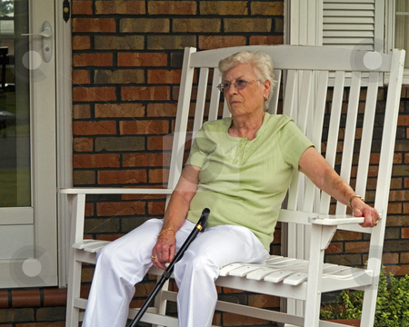 Elderly woman sitting on porch stock photo, Elderly woman with a cane, sitting on a chair on a front porch. by W. Paul Thomas