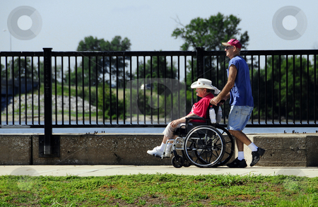 Man pushing woman in wheelchair stock photo, Man pushing a woman in a wheelchair outdoors. by W. Paul Thomas
