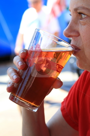 Beer time stock photo, Woman drinking beer on fourth of july celebration by Jack Schiffer
