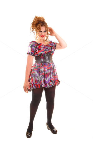 Pretty modern woman. stock photo, Beautiful red haired woman in a colorful dress with a big belt, black pantyhose and high heels standing in the studio wit her hands on the hips. by Horst Petzold