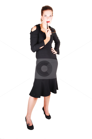 Pretty girl in black dress. stock photo, Young lovely girl in a black dress and sunglasses in her mouth with bright red lips standing in the studio for white background. by Horst Petzold