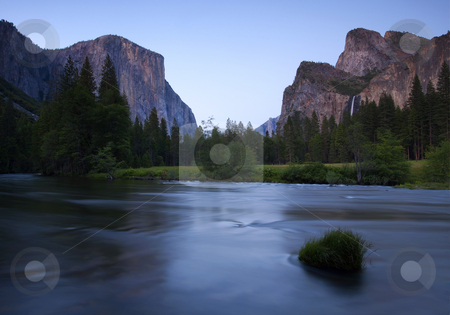Yosemite Twilight stock photo, El Capitan and Bridal Veil Falls flank the Yosemite Valley aglow in the last light of twilight as the Merced River rushes past. by Mike Dawson
