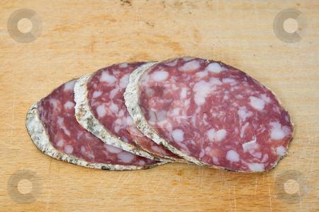 Salami slices stock photo, Salami sliced on cutting board by ANTONIO SCARPI