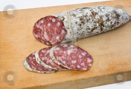 Salami on board stock photo, Salami sliced on cutting board by ANTONIO SCARPI
