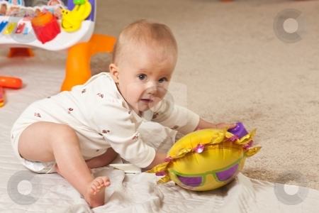 Playing on the floor stock photo, Caucasian baby girl playing on a floor. by Mariusz Jurgielewicz