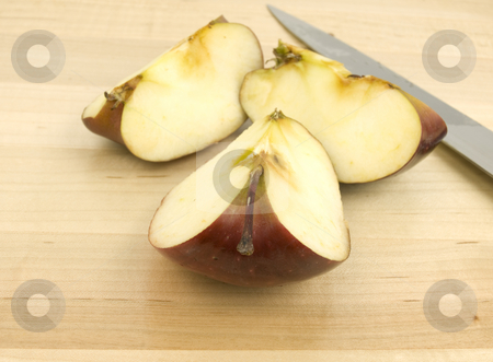 Sliced apple with knife stock photo, Sliced apple with knife on a wooden background by John Teeter