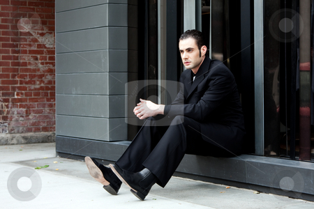 Business man sitting stock photo, Handsome Caucasian business man in black suit sitting on street in front of a modern building by Paul Hakimata