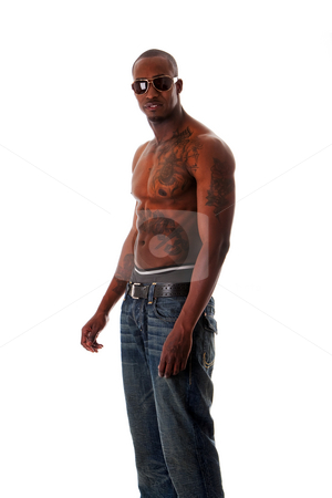 Fit African man stock photo, Handsome fit African American male with tough attitude standing sideways, toned body and tattoos, wearing blue jeans and sunglasses, showing rim of underwear, isolated by Paul Hakimata