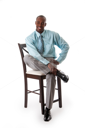 Business man on chair stock photo, Handsome African American business man smiling sitting on chair, wearing sea green shirt and gray pants, isolated by Paul Hakimata