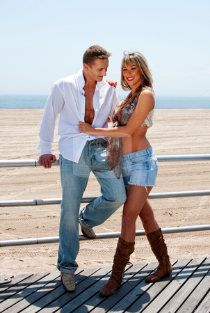 Happy romantic couple stock photo, Young romantic sexy couple, man and woman, next to railing on the boardwalk at the beach standing together being happy and smiling by Paul Hakimata