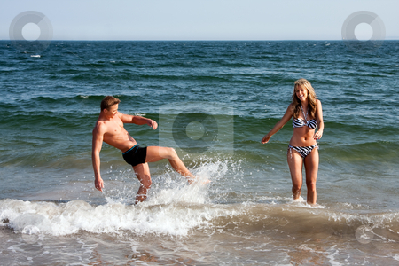 Couple playing in ocean water stock photo, Beautiful young couple playing in the ocean splashing water, heaving fun on a summer day by Paul Hakimata