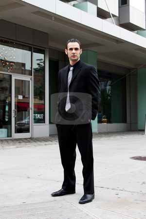 Business man standing stock photo, Handsome Caucasian business man in black suit and hands in pocket standing on street in front of a modern building by Paul Hakimata