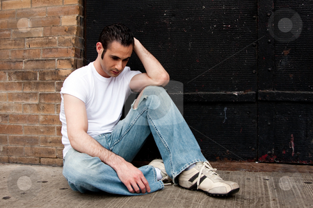 Depressed man stock photo, Handsome Caucasian man dressed in white shirt and blue jeans sitting on concrete floor in front of black metal door with a depressed expression thinking by Paul Hakimata