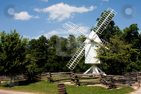White windmill stock photo, A white wooden windmill in a small meadow behind a wooden fence on a summer day with blue skies surrounded by trees. by Paul Hakimata