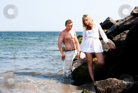 Fashion models at beach stock photo, Caucasian guy and girl together on rock formation next to ocean water. Female is wearing long white shirt. Both standing half in water and half on rocks at the beach. Guy showing muscular abs and bare torso wearing beige pants, heaving cool attitude. Together hanging out. by Paul Hakimata