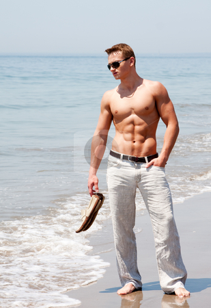 Handsome man standing on beach stock photo, Toned cute handsome male standing on the beach with naked torso showing six pack abs holding shoes in hand wearing sunglasses and hand in pocket by Paul Hakimata