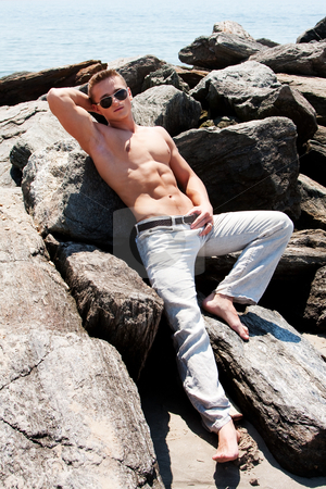 Toned man on rocks stock photo, Sexy handsome male with sunglasses and toned body showing six pack abs on rocks at beach by Paul Hakimata