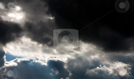 Storm clouds stock photo, The formation of dark thunder storm clouds with a patch of sun light shining through by Paul Hakimata