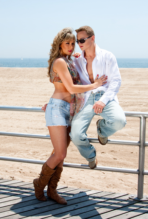 Sexy romantic couple stock photo, Young romantic sexy couple, man and woman, next to railing on the boardwalk at the beach standing together by Paul Hakimata