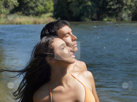 Young couple at river looking up eyes closed stock photo, Mixed young couple outdoors at river looking up eyes closed by Jeff Cleveland