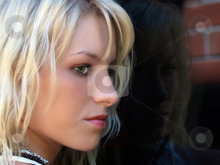 Pretty blond teen profile portrait outdoors window stock photo, Young blond teen girl portrait reflected in window by Jeff Cleveland